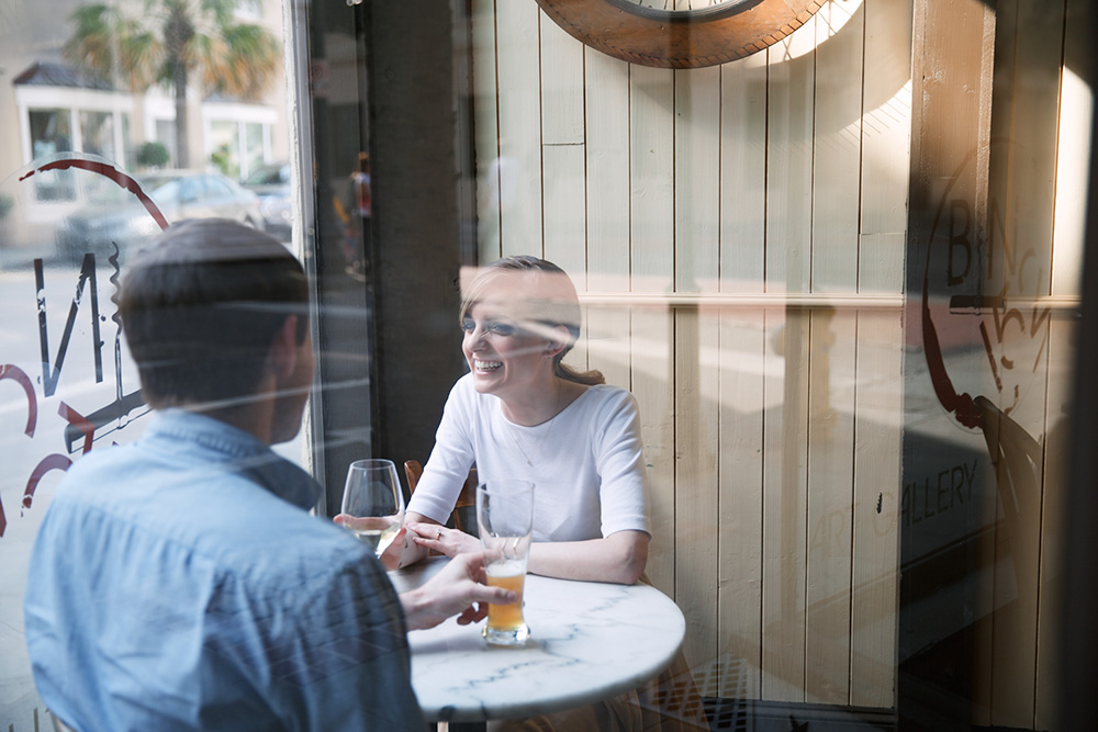 Photo of a couple inside a wine bar, from outside the window; photo by Olivia Rae James