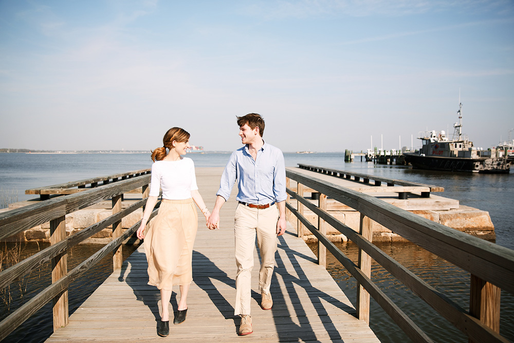 Couple walking on a pier; engagement photo by Olivia Rae James
