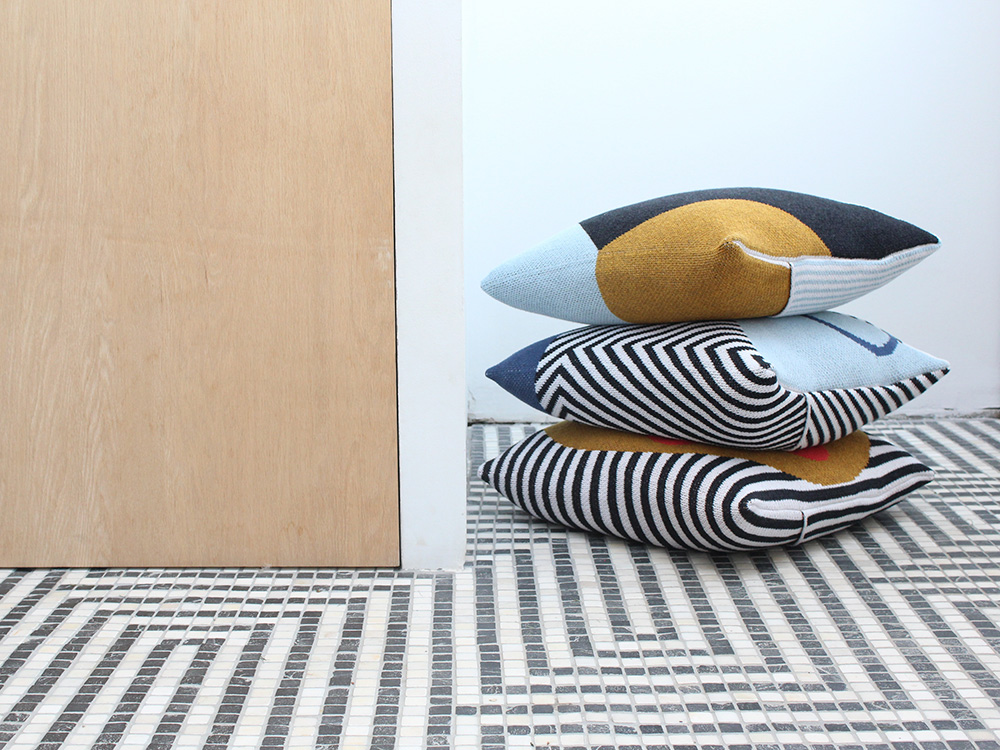 A stack of pillows with geometric patterns, designed by DittoHouse, aka Molly Fitzpatrick