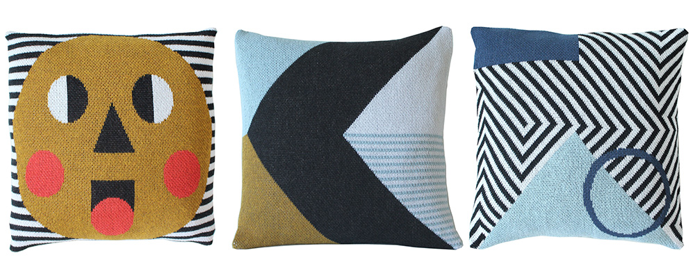 Three pillows in a row, one with a cute face, two with abstract geometric designs; designed by DittoHouse, aka Molly Fitzpatrick