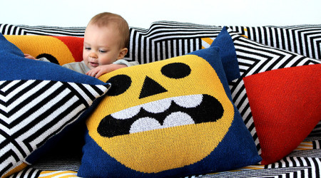 A baby surrounded by colorful pillows designed by DittoHouse, aka Molly Fitzpatrick