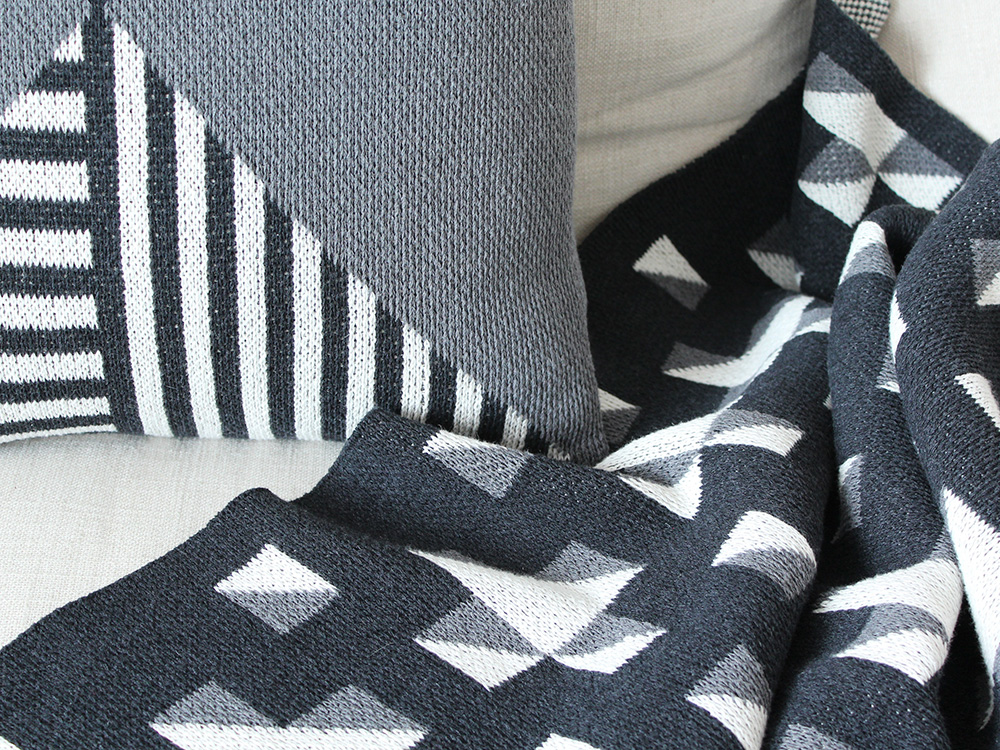A geometric pillow and throw in a grayscale color palette, designed by DittoHouse, aka Molly Fitzpatrick