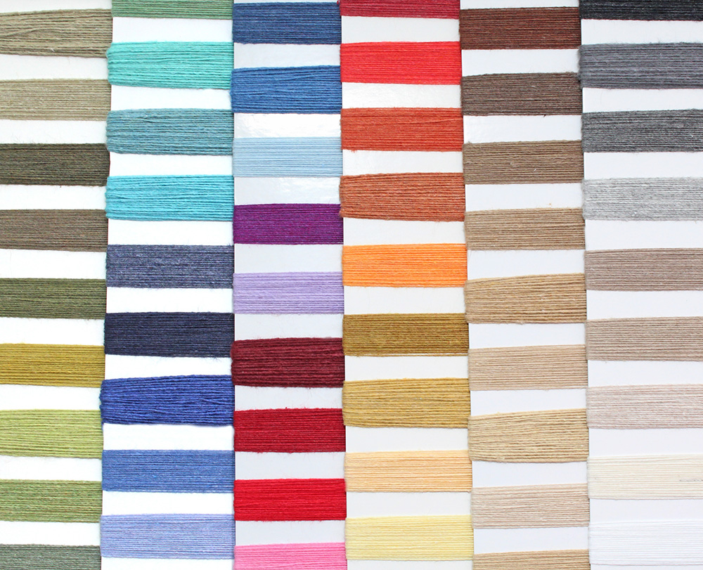 Many colorful swatches of recycled cotton yarn