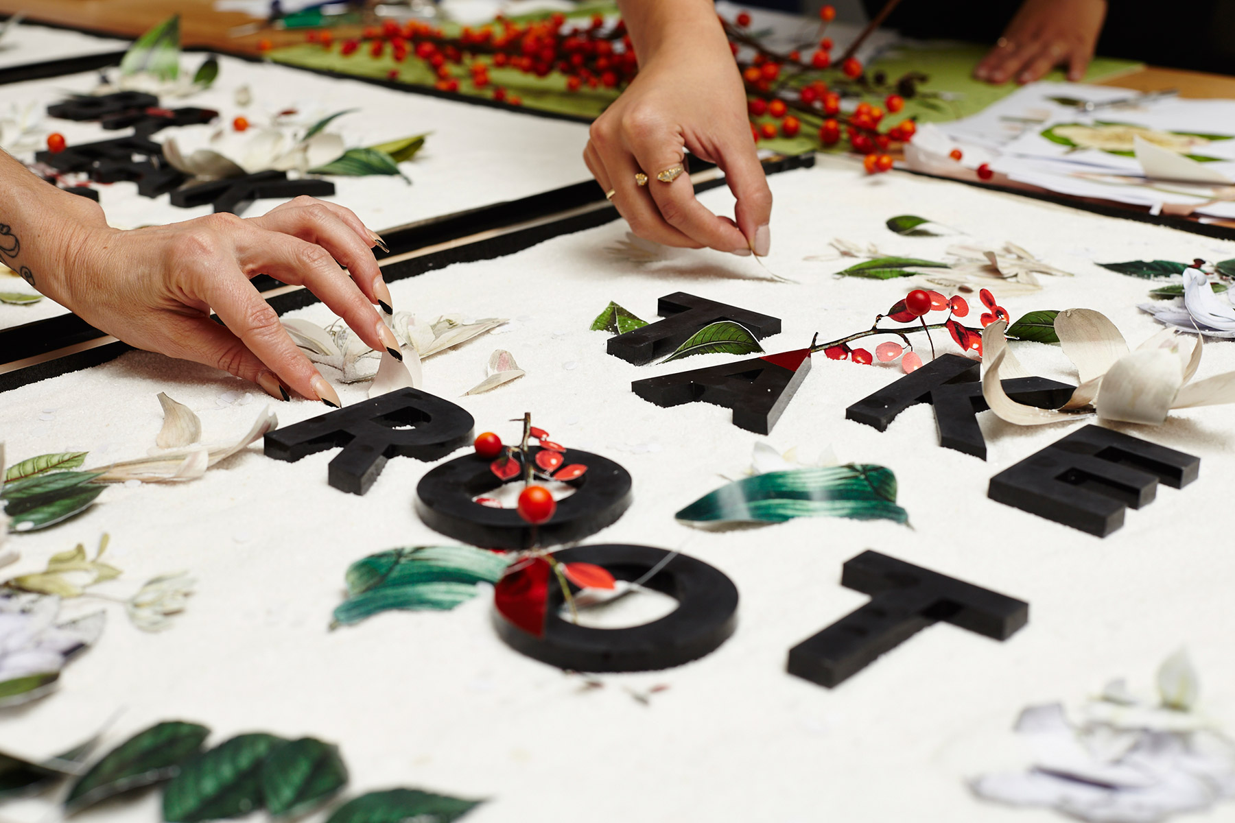 A photo of peoples' hands composing florally-decorated type