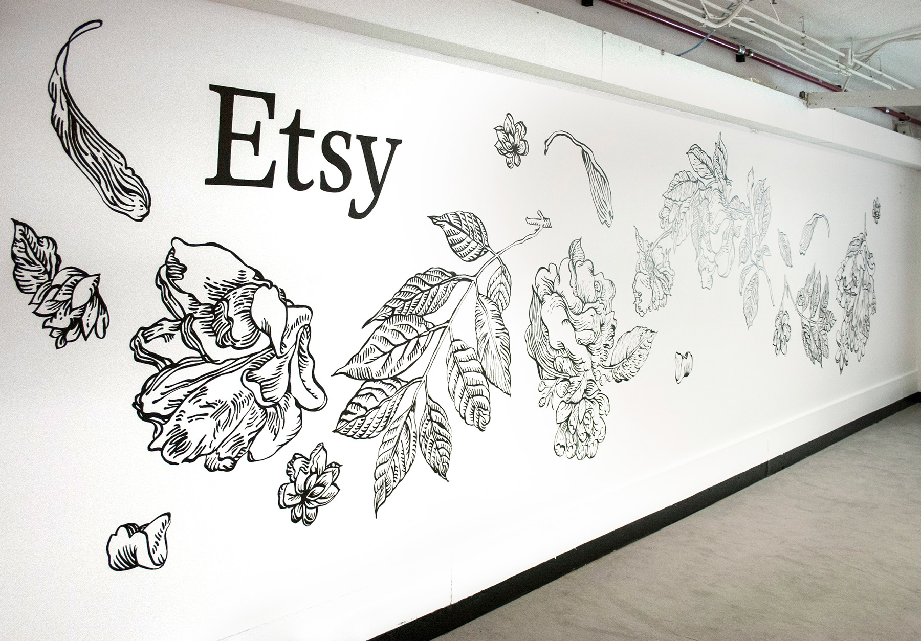 A wall with the Etsy logo and flowers painted on in a black-and-white linear style