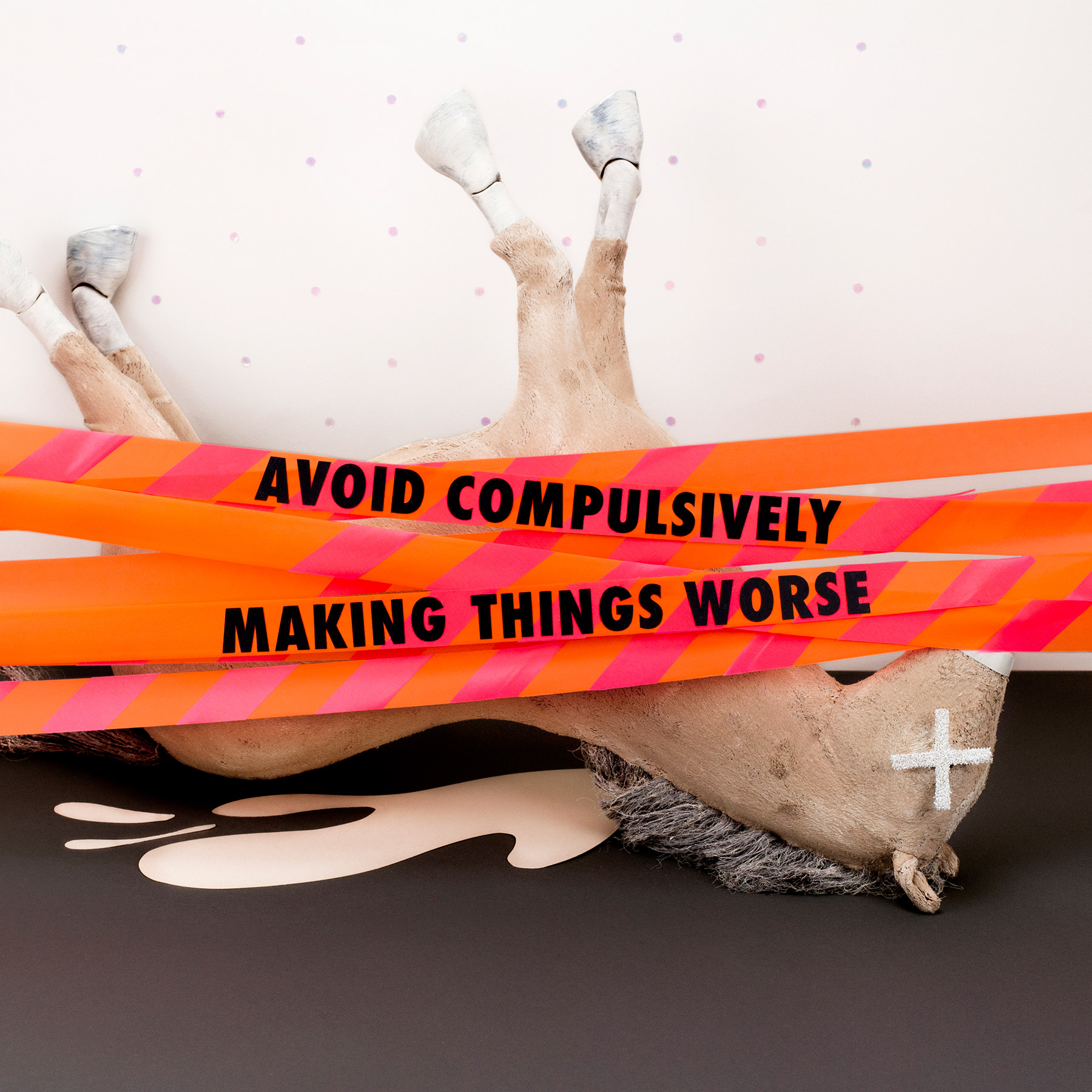 "A dead-looking paper mache horse with caution tape reading ""Avoid compulsively making things worse"""